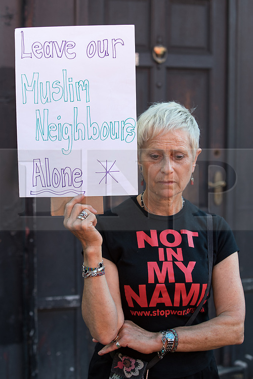 "© Licensed to London News Pictures. 19/06/2017. London, UK. A local resident protests at the scene with a placard reading "" Leave our Muslim neighbours alone "" . One man is known to be dead and several inured after a hired van was driven in to people on Whadcoat Street in Finsbury Park in North London after late night prayers at a nearby mosque . Photo credit: Joel Goodman/LNP"