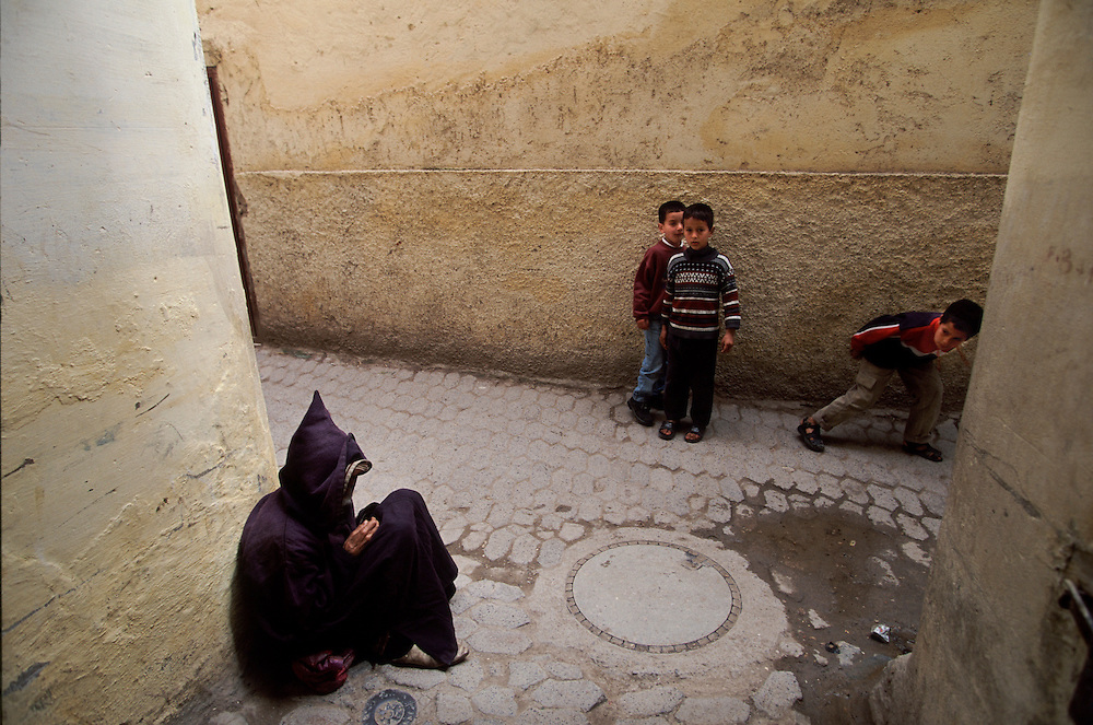 """Children looking at a beggar wearing traditional """"jelaba"""" clothing in one of the tipical narrow streets inside Fez medina."""