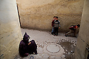 "Children looking at a beggar wearing traditional ""jelaba"" clothing in one of the tipical narrow streets inside Fez medina."