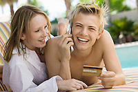 Couple Relaxing Poolside Using Credit Card and Cell Phone