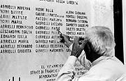 Italia, 2004, dal libro Ci resta il nome. Fragheto (Pesaro). 7 aprile 1944. Il sig. Gabrielli, unico superstite della sua famiglia, indica con la chiave della casa, la stessa dove si compì la strage, i nomi dei parenti uccisi. Nella rappresaglia, vengono uccise 30 persone ad opera di reparti tedeschi della Divisione Herman Göering e squadre della Guardia Nazionale Repubblicana, che non essendo riusciti ad agganciare i partigiani rivolgono la loro ira nei confronti dei civili. Nell'area delle province di Forlì-Cesena e Pesaro, il culmine delle stragi nella zona, si compie a Tavolicci, sulle montagne forlivesi dove il 22 luglio vengono uccise 64 persone, principalmente donne e bambini, mitragliate e bruciate. Al Passo del Carnaio il 25 luglio 26 ostaggi rastrellati nella zona vengono fucilati.Fragheto (Pesaro).  7 April 1944. Signor Gabrielli, the only survivor of his family, points with the key of his house (the same in which the massacre occurred) to the names of the relatives killed. In this reprisal, 30 people were killed by German troops of the Herman Göering Division and by groups of the National Republican Guard, who, unable to capture the partisans, took their frustration out on civilians. The worst massacre to take place in the provinces of Forlì-Cesena and Pesaro was at Tavolicci, in the mountains above Forlì, were on 22 July 64 people, mainly women and children were machine-gunned and burned. On 25 July, at the Carnaio Pass, 26 hostages who had been rounded up in the area were shot. arte, arts, cultura, culture, monument, monumento, sito storico, heritage site