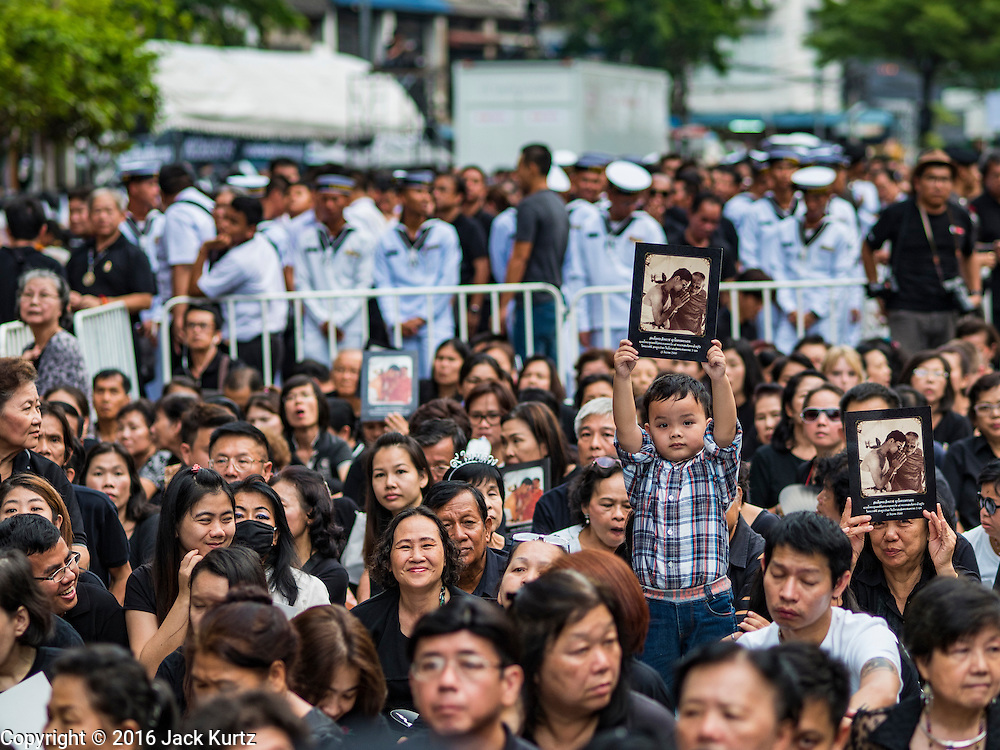26 NOVEMBER 2016 - BANGKOK, THAILAND: A Thai child holds up a photo of the late king during a service in his honor in Bangkok's Chinatown. Thousands of people gathered on Yaowarat Road in the heart of Bangkok's Chinatown to honor Bhumibol Adulyadej, the Late King of Thailand. The event was organized by the Thai-Chinese community and included a performance by the Royal Thai Navy orchestra of music composed by the Late King, a prayer by hundreds of Buddhist monks. It concluded with a candlelight vigil. The King died after a long hospitalization on October 13. The government has declared a one year mourning period. HRH Crown Prince Maha Vajiralongkorn, the Heir Apparent and Late King's son, is expected to be name the King next week. He will be known as Rama X.       PHOTO BY JACK KURTZ