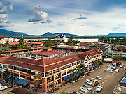"16 JUNE 2016 - PAKSE, CHAMPASAK, LAOS: The uncompleted but already in use Champasak Shopping Center in Pakse. The three story shopping center (only the ground floor is fully open) is more like a market with small family owned shops selling clothes. There is a ""wet"" market (a fruit and produce market) next to it. Pakse is the capital of Champasak province in southern Laos. It sits at the confluence of the Xe Don and Mekong Rivers. It's the gateway city to 4,000 Islands, near the border of Cambodia and the coffee growing highlands of southern Laos.      PHOTO BY JACK KURTZ"
