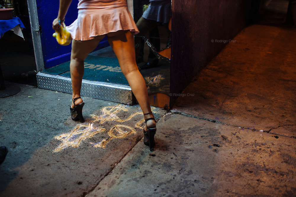 A dancer walks above some symbols used in a ritual to attract lucky and money during working hours at a lap-dancing club in Ciudad Nezahualcoyotl, March 31, 2011.