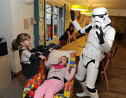 Star Wars, Rachel House, Kinross, 11-12-2016<br /> <br /> People dressed as Star Wars characters to visit children's hospice. Edinburgh 's Capital Sci-Fi Con organiser Keith Armour and other delegates to don costumes and visit children and their families at Rachel House.<br /> <br /> Shannon protects her siser, Erin from a Storm Trooper<br /> <br /> (c) David Wardle | Edinburgh Elite media