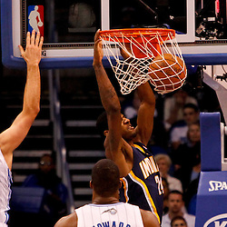 March 11, 2012; Orlando, FL, USA; Indiana Pacers shooting guard Paul George (24) dunks over Orlando Magic power forward Ryan Anderson (33) and center Dwight Howard (12) during the first quarter of a game at  Amway Center.   Mandatory Credit: Derick E. Hingle-US PRESSWIRE