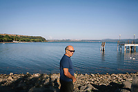 ANGUILLARA SABAZIA (LAKE BRACCIANO), ITALY - 26 JULY 2017: An elderly man walks by Lake Bracciano, whose level has dropped more than 1,50 meters, in Anguillara Sabazia (Lake Bracciano), Italy, on July 26th 2017.<br /> <br /> Lake Bracciano provides eight percent of Rome's water and has sunk about 1.5 meters<br /> <br /> A severe drought and sweltering temperatures have led Rome city officials to consider a potential rationing of drinking water for eight hours a day for a million and a half Rome residents. The water crisis has become yet another sign of man being at the mercy of an increasingly extreme climate, but also of once mighty Rome's political impotence, managerial ineptitude and overall decline.