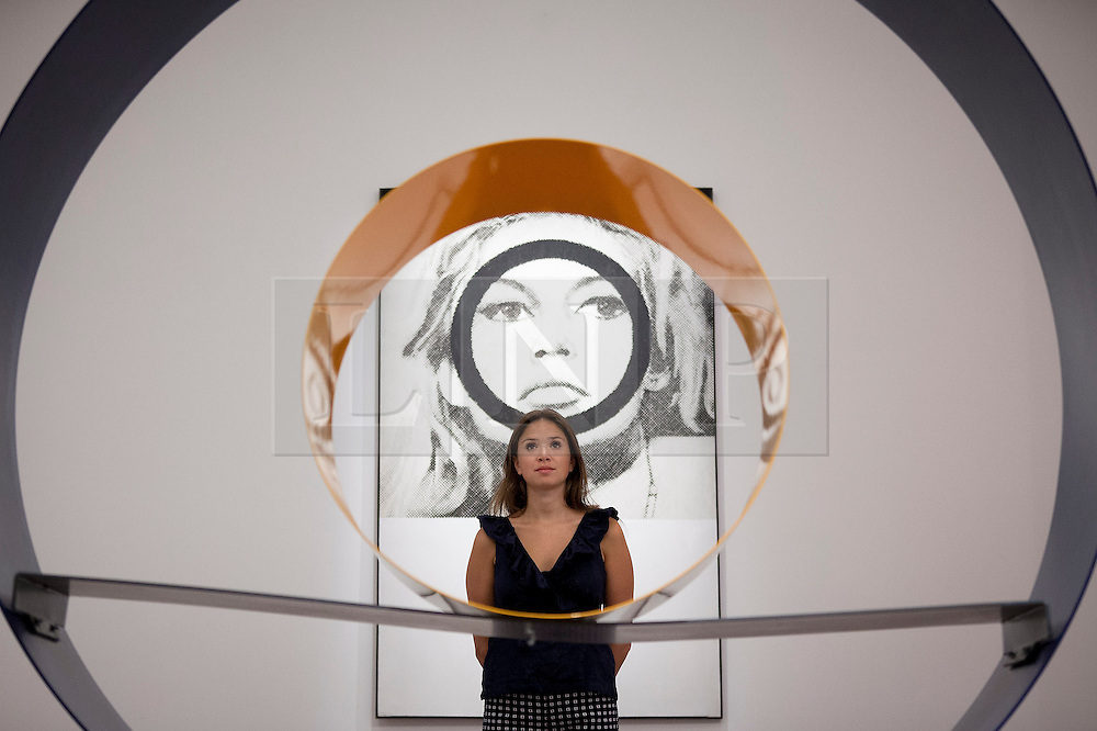 """© Licensed to London News Pictures. 03/09/2013. London, UK. A Sotheby's employee is seen through David Annesley's """"Untitled (Circle)"""" (1966) with Gerald Laing's """"Bridget Bardot"""" (1963) in the background during the press view for an exhibition of art from the 1960's at Sotheby's in London today (03/09/2013). The exhibition, entitled """"The New Situation: Art in London in the Sixties"""" and located at the auction house's New Bond Street building, is open to the public from 4th to the 11th of September 2013. Photo credit: Matt Cetti-Roberts/LNP"""