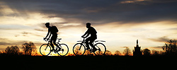 © Licensed to London News Pictures. 28/12/2015. London, UK.  Cyclists at sunrise in Bushy Park. Photo credit: Peter Macdiarmid/LNP