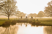 UNITED KINGDOM, London: 18 April 2019 <br /> Cyclists make their way through Richmond Park as the sun rises behind him on what is set to be a warm April's day. Temperatures for the Easter weekend are set to reach 25C.<br /> Rick Findler / Story Picture Agency