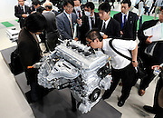 Members of the media look at the engine of Toyota Motor Corp.'s third generation Prius hybrid car during an official unveiling of the vehicle at the automaker's showroom  was in Tokyo, Japan on 18 May 2009.