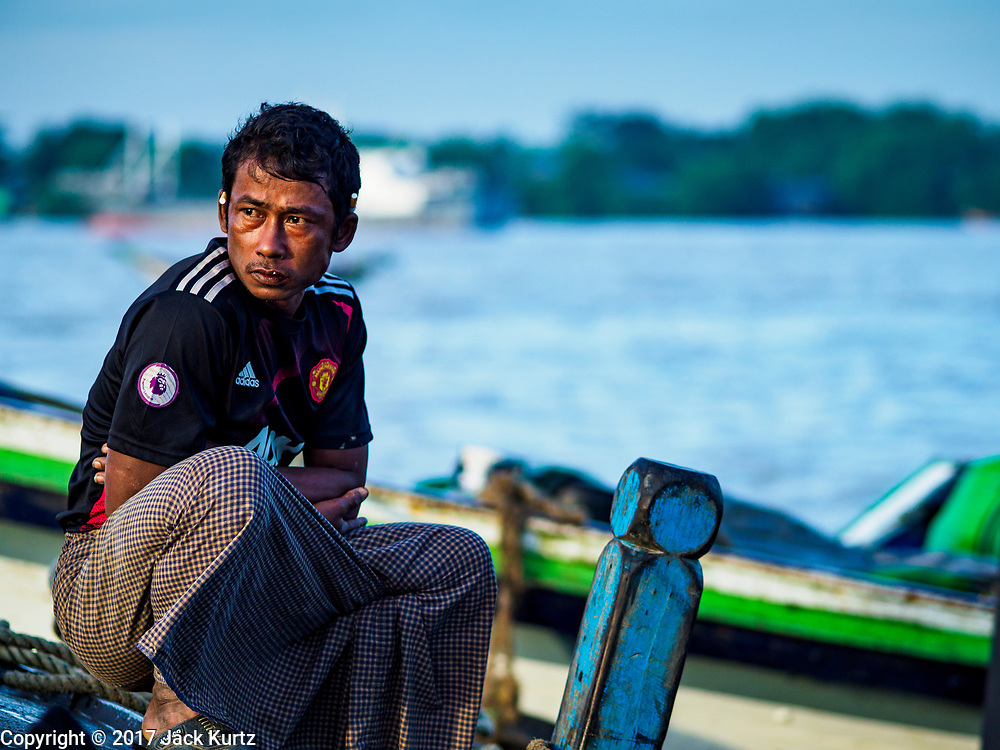 23 NOVEMBER 2017 - YANGON, MYANMAR: A crewman on a fishing boat waits for his boat to be unloaded at the San Pya Fish Market. San Pya Fish Market is one of the largest fish markets in Yangon. It's a 24 hour market, but busiest early in the morning. Most of the fish in the market is wild caught but aquaculture is expanding in Myanmar and more farmed fresh water fish is being sold now than in the past.    PHOTO BY JACK KURTZ