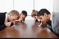 Multiethnic business people sniffing cocaine around conference table