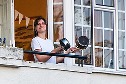 © Licensed to London News Pictures. 09/04/2020.  Hammersmith, West London, UK. A woman bangs cooking pots together from her balcony at 8pm this evening, joining people across the country expressing their gratitude for the NHS, care workers and other key workers who continue to grapple with the coronavirus epidemic, which to date has claimed over 7000 lives nationally. Photo credit: Guilhem Baker/LNP