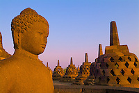 A stone Buddha and an array of stupas greet the rising sun from Borobudur, the world's largest Buddhist temple complex in Java, Indonesia. Travel photography by Djuna Ivereigh.