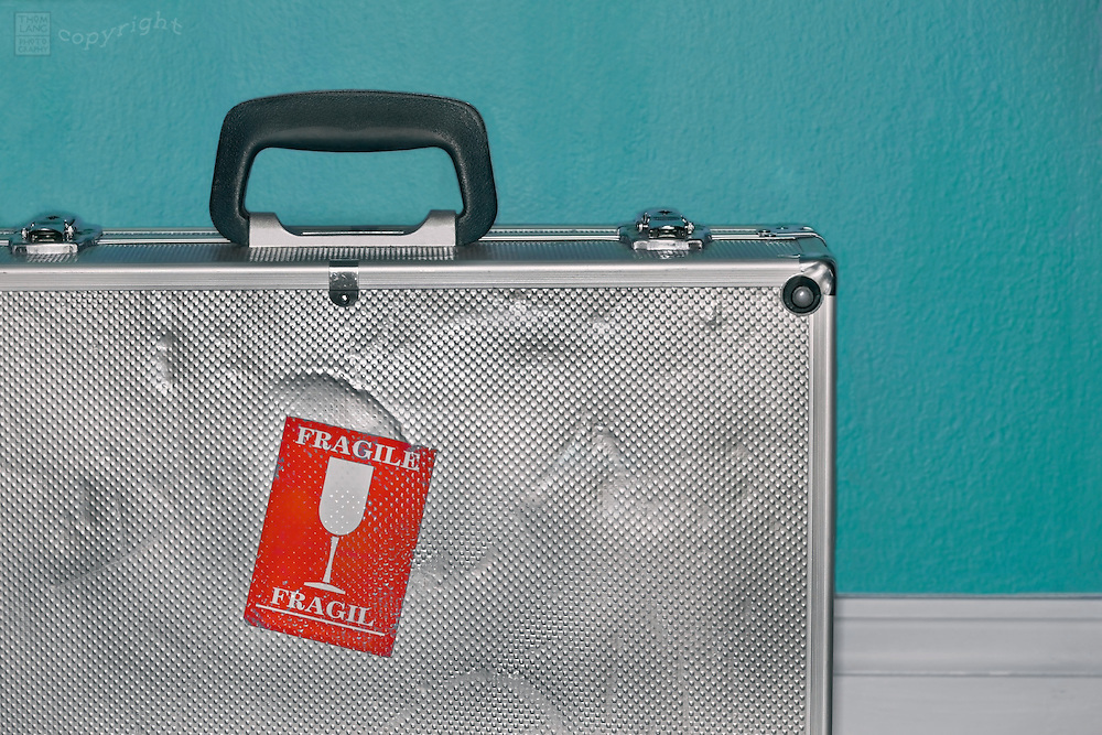 A dented metal suitcase with a red Fragile sticker on it.