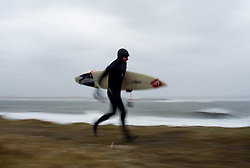 © Licensed to London News Pictures. 23/03/2013..Cleveland, England..Surfer Gabe Davies from Tynemouth heads into the waves as the wintery weather continues to chill the country. Cleveland on the east coast of England suffered freezing cold temperatures and strong winds that brought big seas to the coastline...Photo credit : Ian Forsyth/LNP