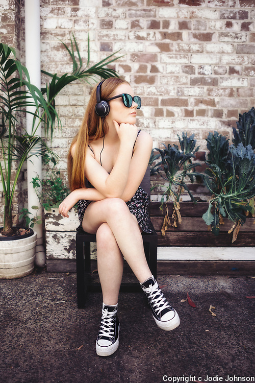Young redhead teenager sitting outside with headphones