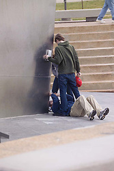 A Bloke flat on his back taking an unusual Photo of Friends at the Saint Louis Gateway Arch on a gray afternoon.