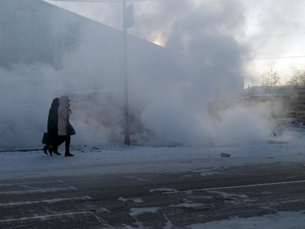Passanten vor entweichendem Wasserdampf aus einer defekten Wasserleitung in Jakutsk. Jakutsk wurde 1632 gegruendet und feierte 2007 sein 375 jaehriges Bestehen. Jakutsk ist im Winter eine der kaeltesten Grossstaedte weltweit mit durchschnittlichen Winter Temperaturen von -40.9 Grad Celsius. Die Stadt ist nicht weit entfernt von Oimjakon, dem Kaeltepol der bewohnten Gebiete der Erde.<br /> <br /> Passersby on a street in Yakutsk. Through a broken warm water pipe condensed water is very fast going up into the air. Yakutsk is a city in the Russian Far East, located about 4 degrees (450 km) below the Arctic Circle. It is the capital of the Sakha (Yakutia) Republic (formerly the Yakut Autonomous Soviet Socialist Republic), Russia and a major port on the Lena River. Yakutsk is one of the coldest cities on earth, with winter temperatures averaging -40.9 degrees Celsius.