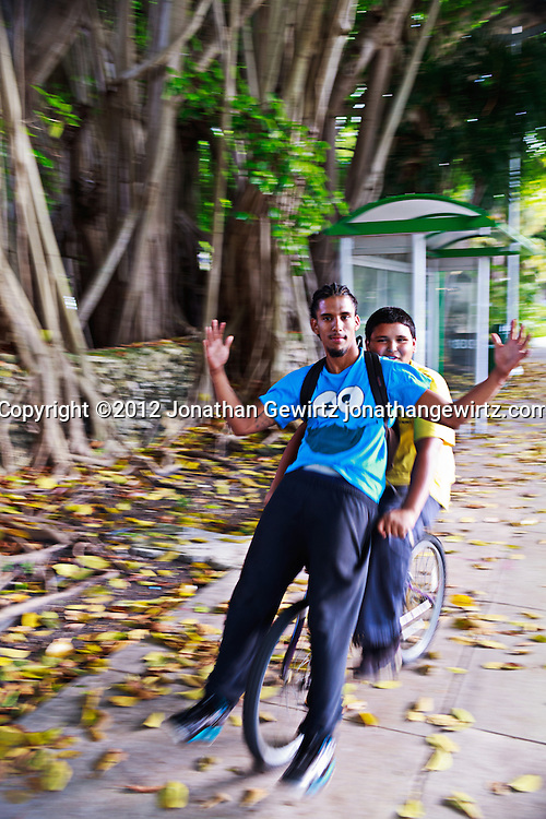 Two young men on a bicycle in Miami, Florida. WATERMARKS WILL NOT APPEAR ON PRINTS OR LICENSED IMAGES.