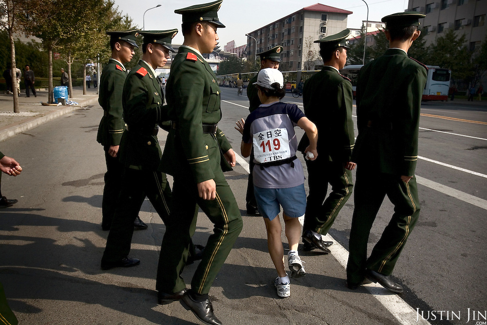 A marathon runner pushes past police patrol in Beijing, which is getting ready to host the 2008 Olympics.