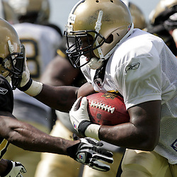04 August 2009: Saints running back P.J. Hill breaks a tackle attempt by cornerback Danny Gorrer (38) during New Orleans Saints training camp at the team's practice facility in Metairie, Louisiana.