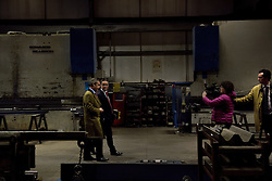 "© London News Pictures. ""Looking for Nigel"". A body of work by photographer Mary Turner, studying UKIP leader Nigel Farage and his followers throughout the 2015 election campaign. PICTURE SHOWS - Nigel Farage gives a 'walk and talk' interview to Channel 4 news at the Concept Metals Factory where he and the party's Economics specialist Patrick O'Flynn introudced their economics policy for the 2015 election in Heywood and Middleton, nr Manchester on March 23rd 2015. . Photo credit: Mary Turner/LNP **PLEASE CALL TO ARRANGE FEE** **More images available on request**"