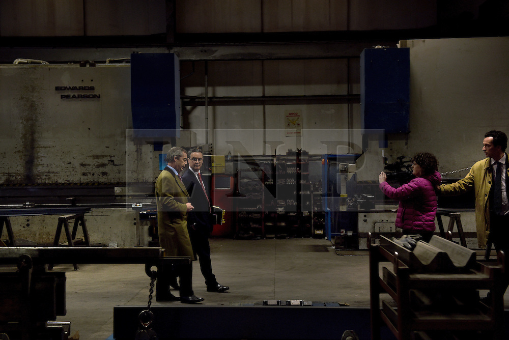 """© London News Pictures. """"Looking for Nigel"""". A body of work by photographer Mary Turner, studying UKIP leader Nigel Farage and his followers throughout the 2015 election campaign. PICTURE SHOWS - Nigel Farage gives a 'walk and talk' interview to Channel 4 news at the Concept Metals Factory where he and the party's Economics specialist Patrick O'Flynn introudced their economics policy for the 2015 election in Heywood and Middleton, nr Manchester on March 23rd 2015. . Photo credit: Mary Turner/LNP **PLEASE CALL TO ARRANGE FEE** **More images available on request**"""