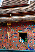 Image of a woman looking out a window at the Red Chapel, Wat Xiengthong, Luang Prabang, Laos.