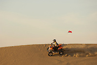Man riding quad bike on sand