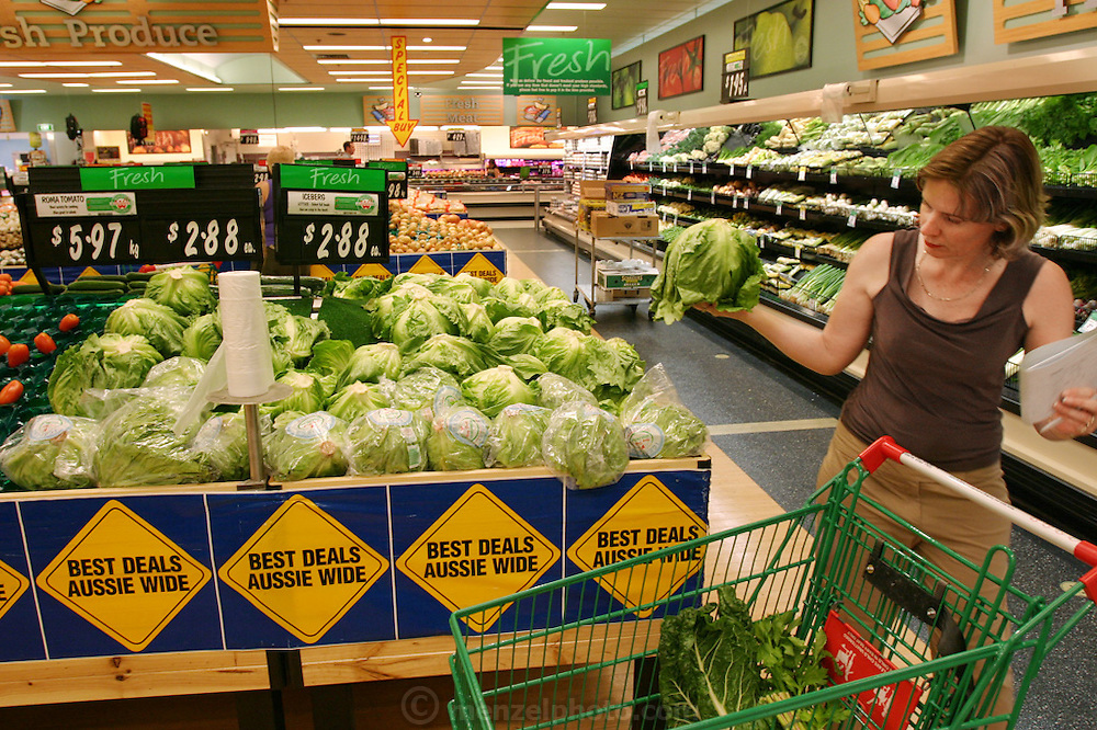 (MODEL RELEASED IMAGE). Natalie Molloy of Brisbane, Australia, puts a lot of thought, and ingredients, into her dinner salads, though not a lot of dressing. Shopping for the evening's meal, she buys English spinach, tomatoes, carrots, cucumber, avocado, mung beans, capsicum (peppers), snap peas, and corn; though decides against the iceberg lettuce in her hand. Hungry Planet: What the World Eats (p. 35).