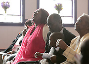 Gloria Collum, left, mother of Teaira Batey, cries out during funeral services for Batey at the Cornerstone Missionary Baptist Church in Gary. Clinton and his son Trayvon sit to the right of Collum.