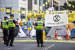 © Licensed to London News Pictures. 17/07/2019. Leeds, UK. Police watch over the Extinction Rebellion protest as it enters its third day in Leeds where activist's have blocked Victoria Bridge in the city centre with a boat & tents. The protest is part of Extinction Rebellion's 'summer uprising' campaign, which has seen similar blockades in London, Cardiff, Bristol and Glasgow & is expected to last until Friday. Photo credit: Andrew McCaren/LNP
