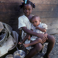 Haiti, Port-au-Prince, Young girl holds brother on her lap in Cite Soleil slum in the capital city