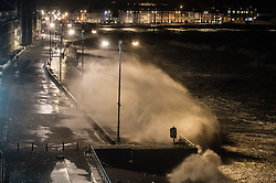 """© Licensed to London News Pictures. 12/02/2014. Aberystwyth, UK. At hight tide this evening (just after 7pm) the police and Coastguards once again closed the seafront promenade to all vehicles and pedestrians as huge waves broke over the sea wall. Winds gusting up to 107mph are battering the west wales coast at Aberystwyth.  Met Office """"red warnings"""",  the first of the winter , indicating risk to life and severe structural damage have been issued.. Photo credit : Keith Morris/LNP"""