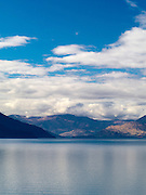 Lake Wakatipu, one of New Zealand's most beautiful lakes, surrounded by mountains and set off by clouds and blue sky on an autumn day.