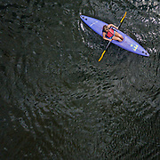 A kayaker aimlessly floats around a lake.