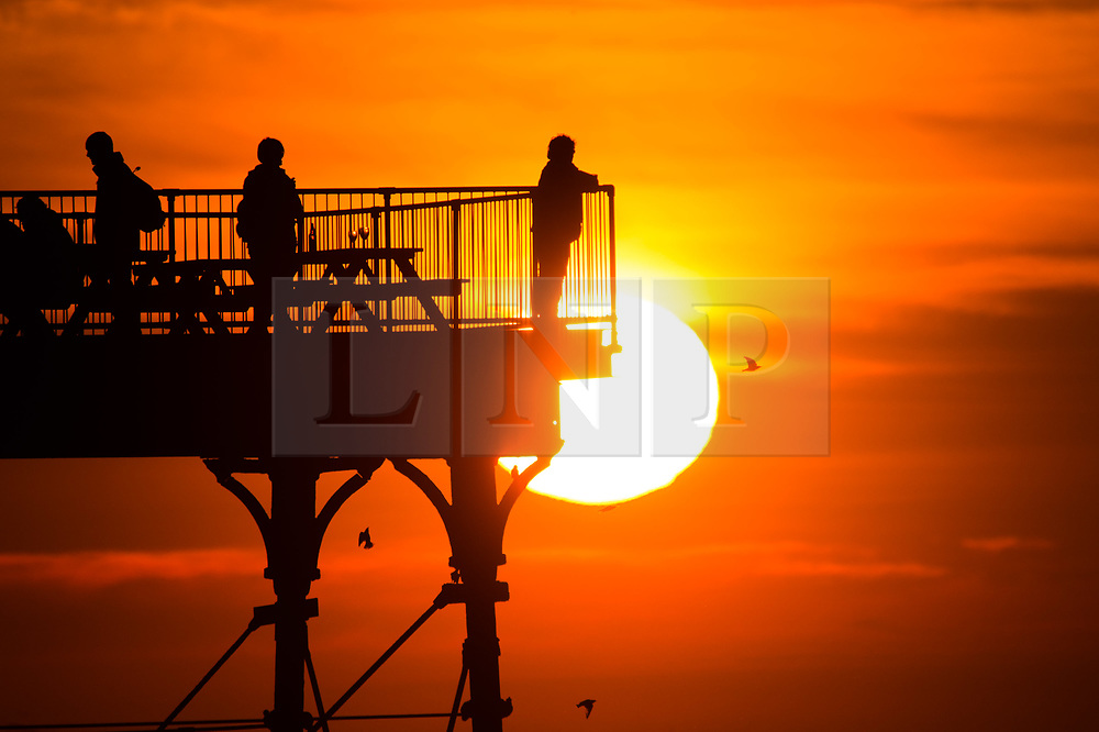 © Licensed to London News Pictures. 25/02/2019. Aberystwyth, UK. The sun sets dramatically behind people standing on Aberystwyth pier at the end of a day or record breaking temperatures and unbroken sunshine. Trawsgoed, a few miles inland of the town, recorded 21.3º celsius, the highest temperature ever recored in the UK in February. .. Photo credit: Keith Morris/LNP