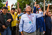 12 MAY 2014 - BANGKOK, THAILAND:  SUTHEP THAUGSUBAN and his supporters sing the Thai national anthem while they block Phichai Road near the Parliament building in Bangkok. Several thousand protestors with the People's Democratic Reform Committee (PDRC) blocked access to the Thai Parliament building in Bangkok as a part of their continuing anti-government protests. The Parliament is not currently in session and was dissolved by former Prime Minister Yingluck Shinawatra but the Senate is in session. The protestors are demanding that the Senate dissolve the current Pheu Thai caretaker government and appoint a new Prime Minister and cabinet. Members of the Senate leadership met with Suthep Thaugsuban Monday to discuss the impasse.  PHOTO BY JACK KURTZ