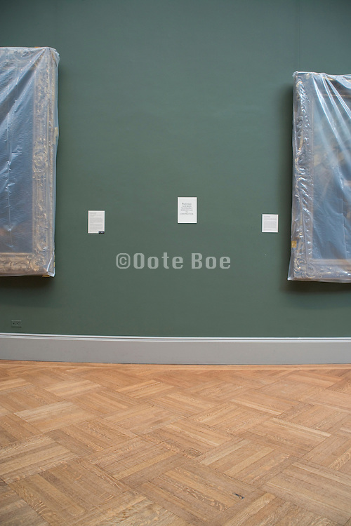 two paintings covered with semi clear plastic in a museum show room Metropolitan Museum of Art