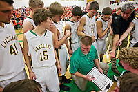 Rodney Dingman takes part in a team huddle with Lakeland High's varsity basketball team during the Prairie Pig basketball game Tuesday, Jan. 24, 2012 against Post Falls High in Rathdrum, Idaho.