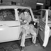 A Studebaker worker installs a door striker on a 1960 Studebaker Lark at the company's South Bend, Indiana plant.
