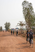 VSO ICS volunteers cycling through the streets of the village of Banteay Char, near Battambang, Cambodia. Bicycles are the easiest and safest way for them to get around the village.