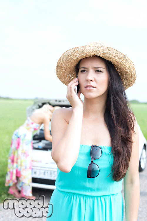 Worried woman using mobile phone while friend examining broken down car at countryside
