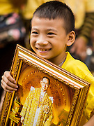 05 DECEMBER 2014 - BANGKOK, THAILAND:  A boy with a portrait of Bhumibol Adulyadej, the King of Thailand, in the plaza at Siriraj Hospital on the King's 87th Birthday. Thousands of people jammed into the plaza hoping to catch a glimpse of the revered Monarch. He was scheduled to make a rare public appearance in the Grand Palace but cancelled at the last minute on the instructions of his doctors. He has been hospitalized in Siriraj Hospital, across the Chao Phraya River from the Palace, since early October.   PHOTO BY JACK KURTZ
