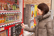 A young Japanese lady using a drink vending machine. Notice the blue price labels are for cool drinks, and red is for warmed drinks, also the grey electronic e-money sensor by the coin and note receptacles.
