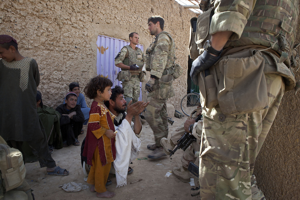 An Afghan interpreter assists British soldiers of 16 Air Assault Bde's elite BRF (Brigade Reconnaissance Force) as they question Afghan locals whilst searching compounds as part of  an operation in the village of Kakaran in Helmand Province, Southern Afghanistan on the 15th of March 2011.