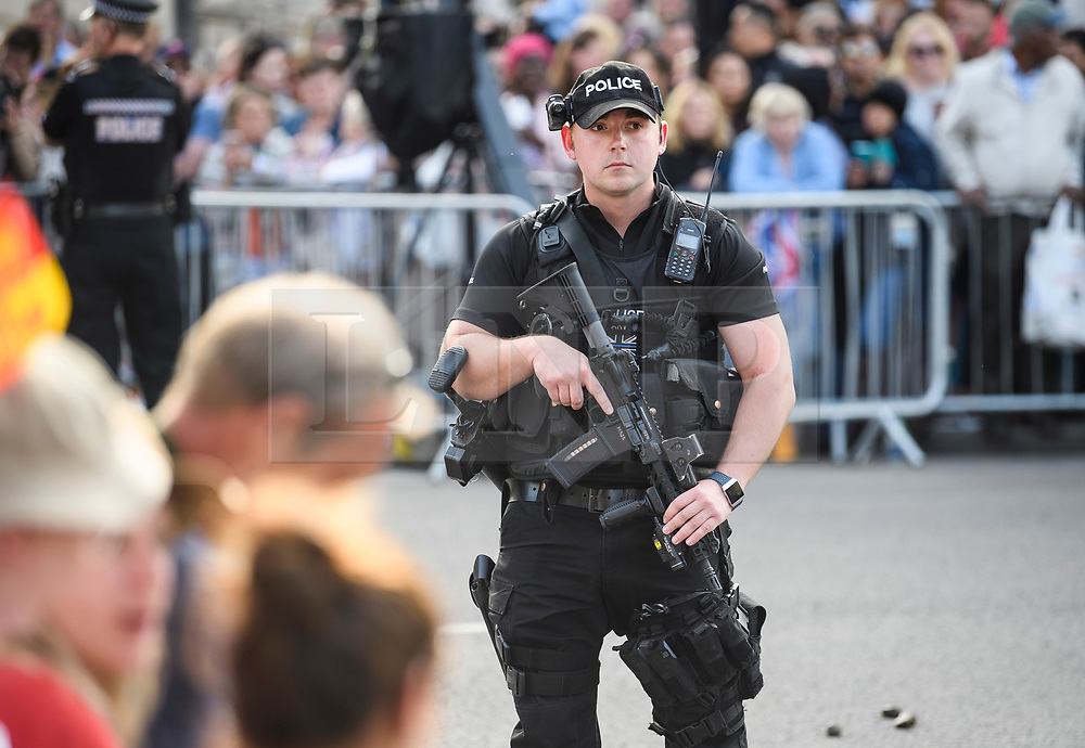 © Licensed to London News Pictures. 18/05/2018. London, UK. An armed police officer watches over members of the public outside Windsor Castle, where Prince Harry and Meghan Markle are to be married tomorrow (Saturday) at St George's Chapel. Photo credit: Ben Cawthra/LNP
