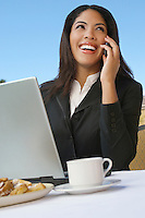 Mid adult business woman talking on phone in front of laptop